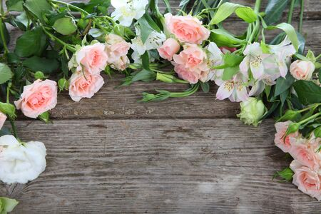 Beautiful bouquet of different flowers on a wooden table photo
