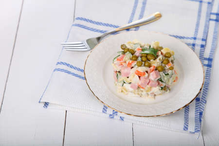laurence: Salad Olivier on a white plate on a wooden table Stock Photo