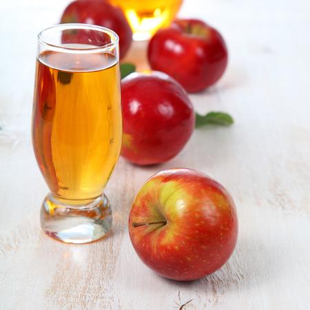vaso de jugo: Zumo de manzana y manzanas en una mesa de madera Foto de archivo