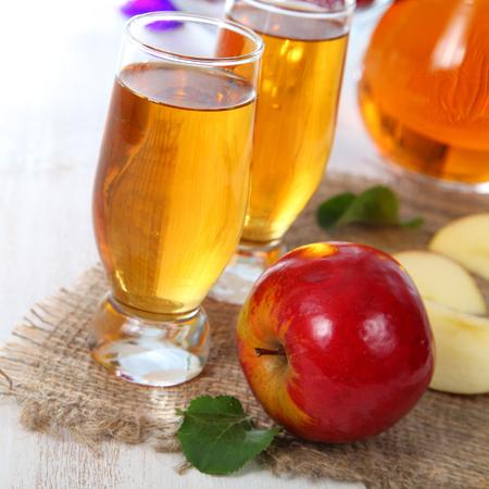 jugo de frutas: Zumo de manzana y manzanas en una mesa de madera Foto de archivo