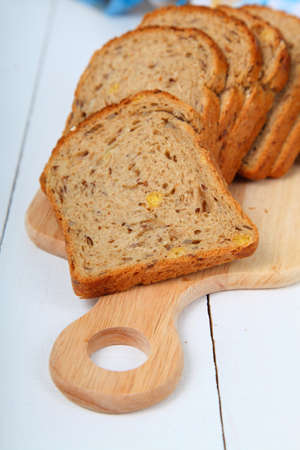 troche: Sliced bread on a wooden board on the table