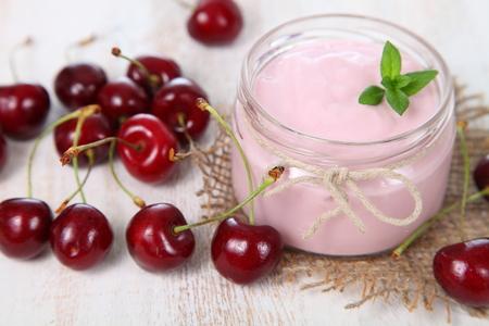 cereza: Yogur de la cereza y cereza madura sobre una mesa de madera. Postre del verano.