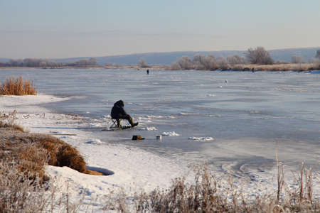 natural ice pastime: Fishermen on the snow-covered lake. Winter landscape. Stock Photo