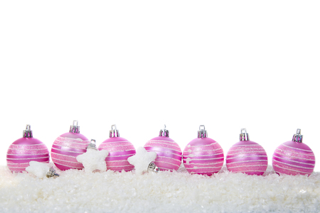 Pink balls and stars in snow isolated on white background. Christmas composition.