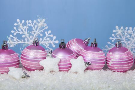 pink christmas: Pink Christmas balls in the snow on a blue background Stock Photo