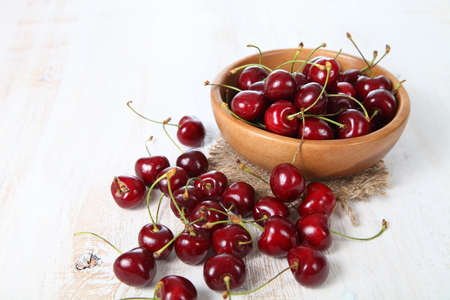Ripe cherry in a wooden bowl on the table