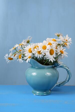 Beautiful chamomiles in a blue jug on wooden table