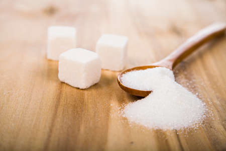 sugar spoon: Sugar in a wooden spoon on the table