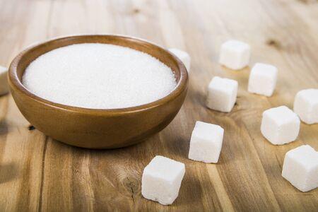azucar: El azúcar en un recipiente de madera sobre la mesa