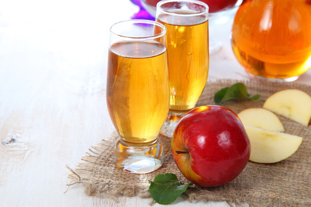 glass cup: Apple juice and fresh red apples on a  wooden table