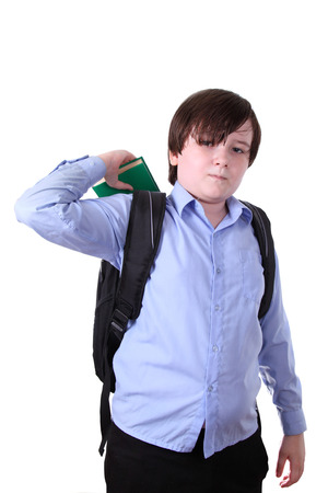 Schoolboy putting a book in a backpack, isolated on a white background