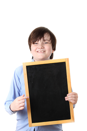 Happy schoolboy  holding a blackboard, isolated on a white background