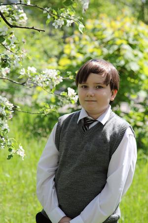 schoolboy: Schoolboy  in spring blossoming garden