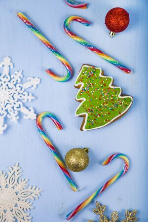 Gingerbread and candy canes on a blue wooden background. Christmas sweets and decorations