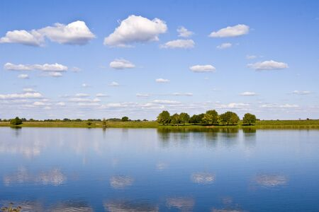 Beautiful landscape with  river and  blue sky with clouds. Trees on the river bank reflected in the water.