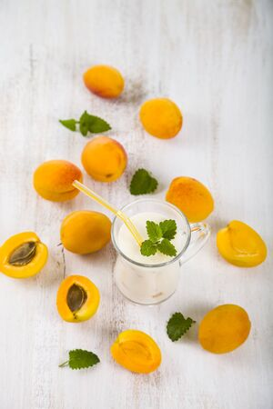 Apricot smoothie or yogurt and ripe apricots on a wooden table. Delicious milk drink with ripe apricots.