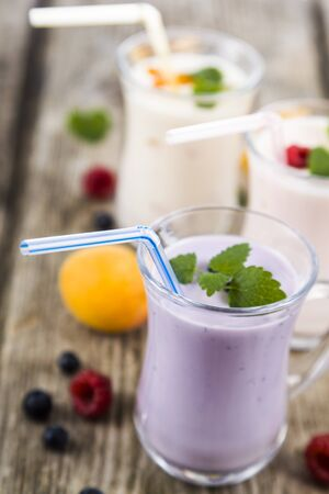 Three glasses with smoothies or yogurt with fresh berries on a wooden table. Milkshakes with raspberries, blueberries, apricots and mint leaves. Stock Photo