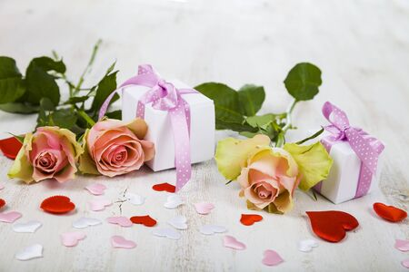 Pink roses,  gift and hearts on a wooden background. Greeting card with Valentines Day, Birthday or Wedding.