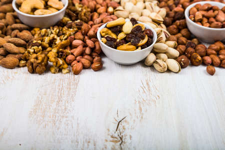Nuts in a plate on a light wooden table. Different kinds of tasty and healthy nuts.