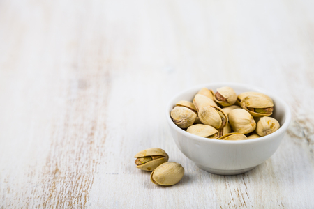 Pistachios in a white bowl on a wooden table close-up. Tasty and healthy nuts. Reklamní fotografie