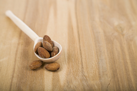 Almonds in a spoon on a wooden table close-up. Tasty and healthy nuts. Top view. Stock Photo