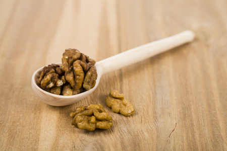 Walnuts in a spoon on a wooden table close up. Tasty and healthy nuts.