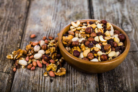 Nuts in a wooden bowl  on a  wooden table. Different kinds of tasty and healthy nuts. Stock Photo
