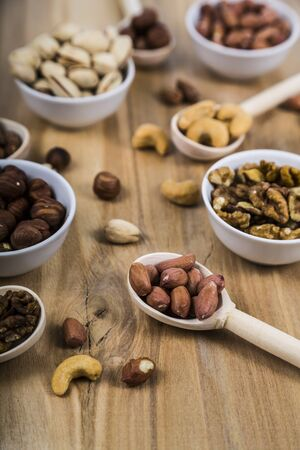 Nuts in a wooden spoons and bowls on a  wooden table. Different kinds of tasty and healthy nuts. Stock Photo