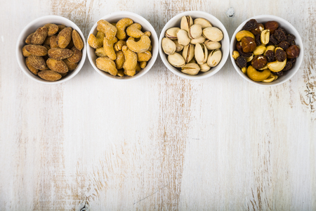 Nuts in a plate on a  wooden table. Different kinds of tasty and healthy nuts.
