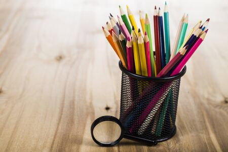 Back to school. Color pencils and magnifier on a wooden table.