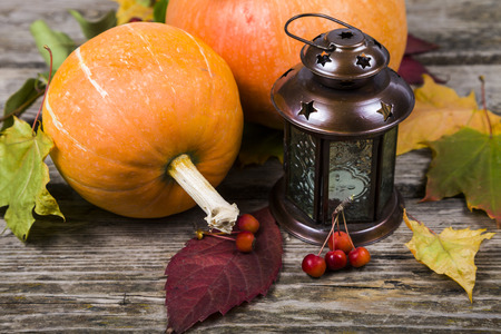 Pumpkins,lantern and fall leaves on an old wooden table Stock Photo