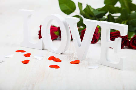 res: Red roses and the word Love on a  wooden background. Greeting card with Valentines Day, Birthday or Wedding.