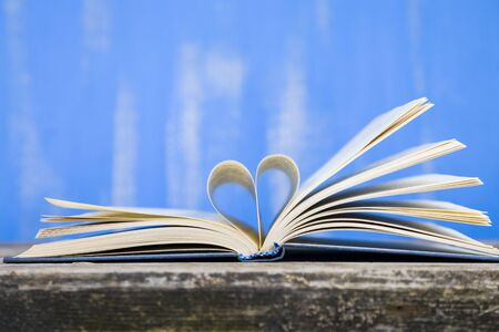 Open book on a wooden table on a blue background. Pages of the book in the form of a heart.