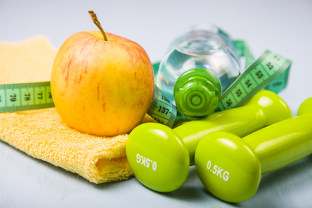 Dumbbells, an apple, a towel and a bottle of water on a blue wooden table. Concept of fitness and a healthy lifestyle.