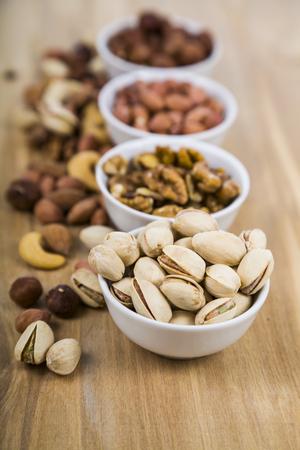 木製テーブルの上のナットを 4 つのボウル。おいしいと健康的なナッツの種類。トップ ビュー 写真素材