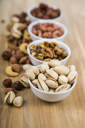Four bowls with nuts on a  wooden table. Different kinds of tasty and healthy nuts. Top view