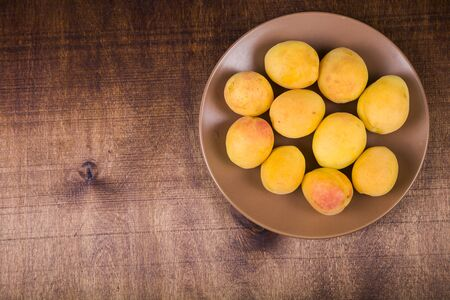 Apricots in a plate on a wooden table. Delicious and healthy dessert close-up, healthy diet.
