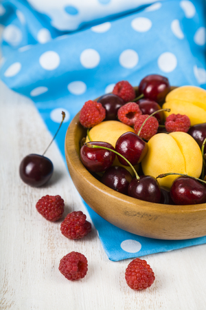 Ripe berries in a plate on a wooden table. Delicious and healthy dessert close-up, healthy diet.