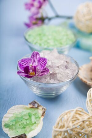 Spa treatments on a blue wooden table. Sea salt, soap and orchid close-up. Stock Photo