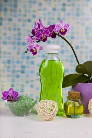 Spa treatments in the bathroom. Sea salt, soap and orchid close-up. Stock Photo