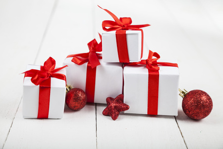 gifts with red bows and christmas decorations on a white wooden background congratulations on new - Christmas Decorations Bows