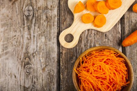 Grate  carrots in a bowl and sliced carrots on a cutting board, top view. Tasty and healthy food. Diet. Stock Photo
