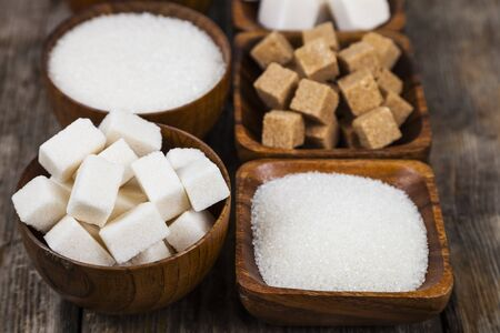 Six bowls of sugar  on an old wooden background. Stock Photo