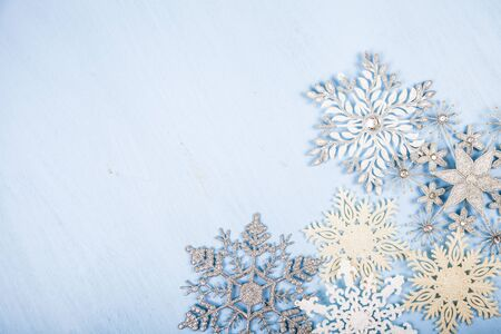 Silvery snowflakes on a blue wooden background. Christmas decor. Stock Photo