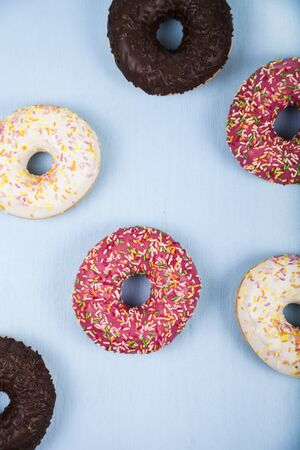 Multicolored donuts close-up on a wooden background. Delicious dessert.