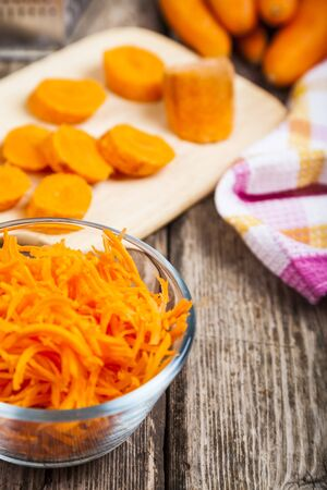 Grate  carrots in a bowl on a wooden table. Tasty and healthy food. Diet.