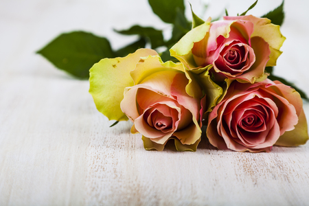 Bouquet of pink roses on a wooden background. Greeting card with Valentines Day, Birthday or Wedding.