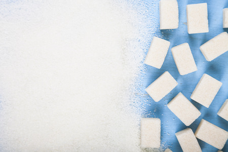 White sugar and cubes of sugar on an old wooden background