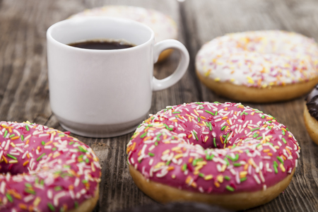 Donuts and a cup of coffee on a wooden background. Delicious breakfast.