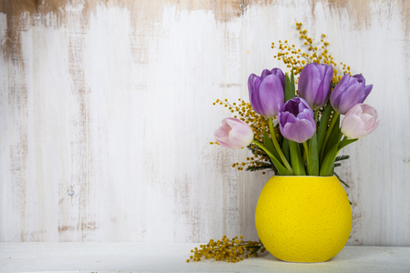 Bouquet of tulips and mimosa in a yellow vase on a wooden background. Still life with beautiful flowers on holiday.